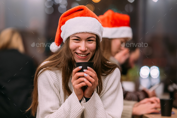 Girl wearing Santa hat sitting in coffee shop and drinking coffee - Stock Photo - Images