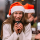 Girl wearing Santa hat sitting in coffee shop and drinking coffee - PhotoDune Item for Sale