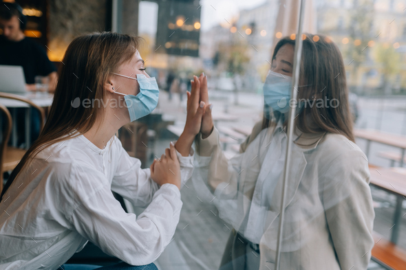 Two women in protective masks opposite each other, window between them - Stock Photo - Images