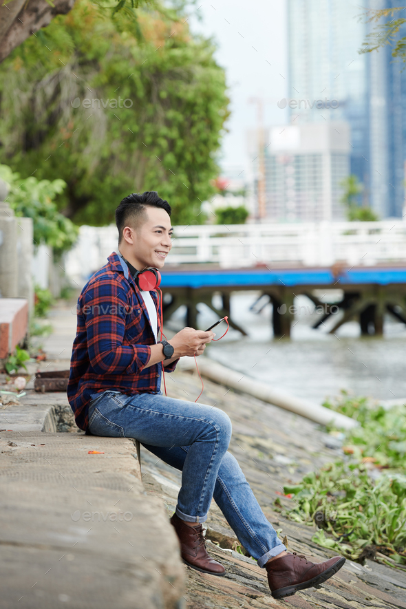 Dreamy Asian Man Choosing Track on Smartphone - Stock Photo - Images