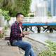 Dreamy Asian Man Choosing Track on Smartphone - PhotoDune Item for Sale