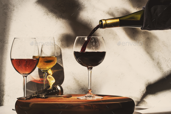 Wine tasting. Red wine pouring into glass on background with selection of red, white and rose wines - Stock Photo - Images