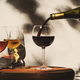 Wine tasting. Red wine pouring into glass on background with selection of red, white and rose wines - PhotoDune Item for Sale