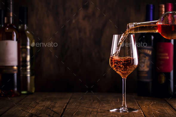 Wine tasting. Rose wine pouring into glass on wooden background - Stock Photo - Images