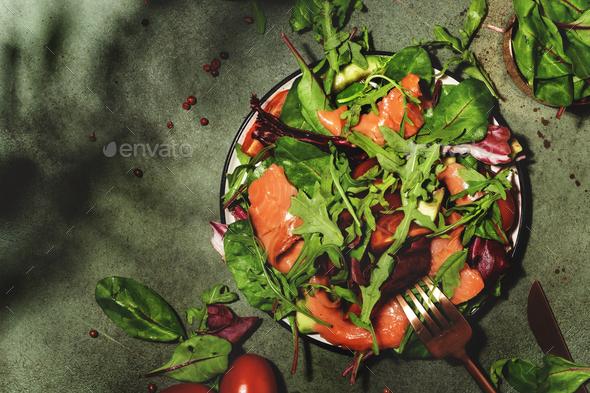 Salmon salad with arugula, beet leaves, radicchio, tomatoes, lemon and olive oil dressing - Stock Photo - Images