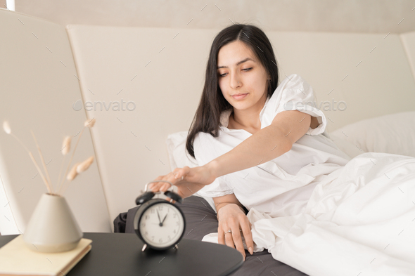 Young female stopping alarm clock - Stock Photo - Images