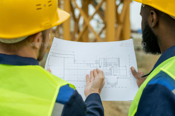 Two intercultural male builders discussing sketch - Stock Photo - Images