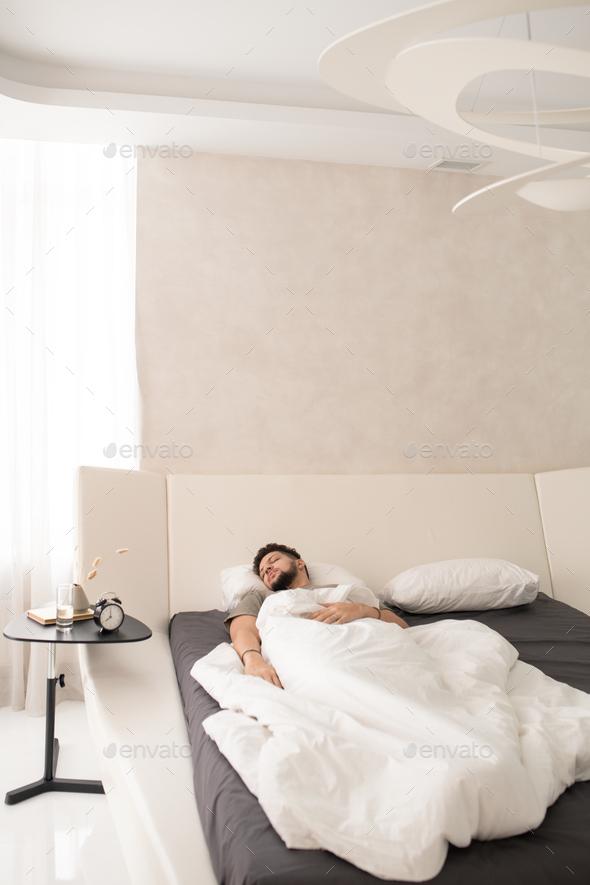 Restful guy sleeping under white sheets - Stock Photo - Images