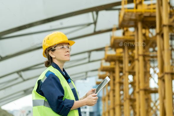 Happy female engineer looking at huge construction frame - Stock Photo - Images