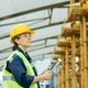Happy female engineer looking at huge construction frame - PhotoDune Item for Sale