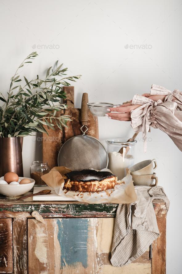 Female hands sprinkling sugar powder over San Sebastian cheesecake - Stock Photo - Images