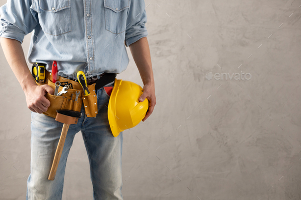 Man worker holding construction helmet and tool belt near wall. Male hand and construction tools - Stock Photo - Images