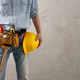 Man worker holding construction helmet and tool belt near wall. Male hand and construction tools - PhotoDune Item for Sale