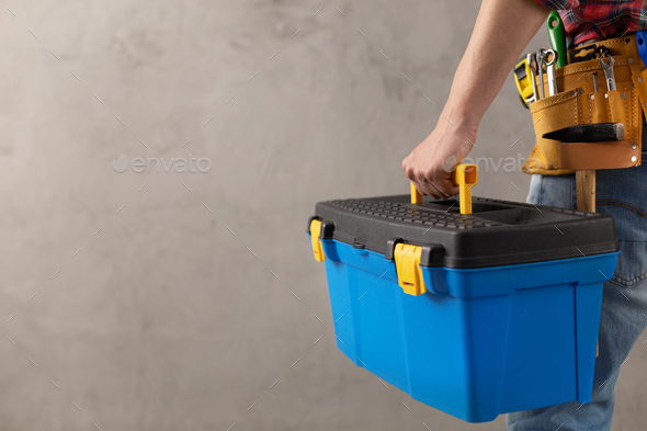 Man worker holding toolbox and tool belt near wall. Male hand and construction tools - Stock Photo - Images