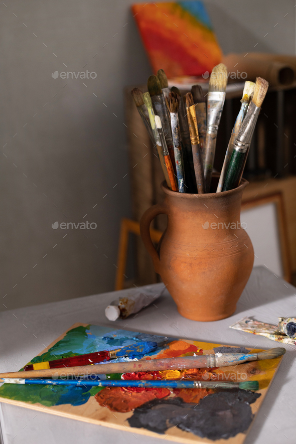 Paint brush in clay jug and palette at tabe. Art still life with painting and painter tool - Stock Photo - Images