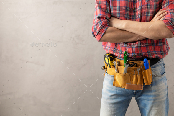 Man worker and tool belt near wall. Male hand and construction tools. Renovation concept - Stock Photo - Images