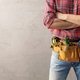 Man worker and tool belt near wall. Male hand and construction tools. Renovation concept - PhotoDune Item for Sale