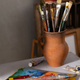 Paint brush in clay jug and palette at tabe. Art still life with painting and painter tool - PhotoDune Item for Sale