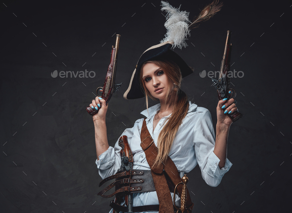 Woman corsair wearing shirt and hat with guns - Stock Photo - Images
