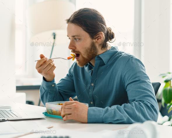 Hungry man enjoying vegan meal during lunch break - Stock Photo - Images