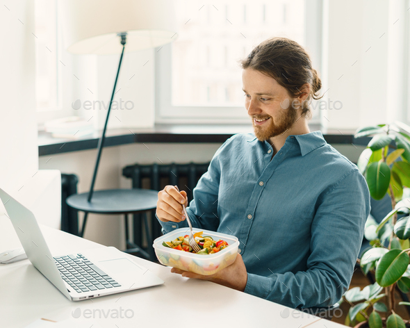 Sitisfied male employee eating vegetarian food at work - Stock Photo - Images