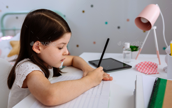 Girl studying at home with mask on table - Stock Photo - Images