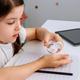 Girl applying hand sanitizer while doing homework - PhotoDune Item for Sale
