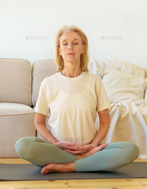 Retired woman meditating and practicing yoga while sitting in lotus pose on floor at home, vertical - Stock Photo - Images