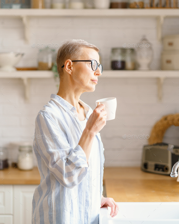 Beautiful senior woman with cup of coffee or rure water looking in window while enjoying new day at - Stock Photo - Images