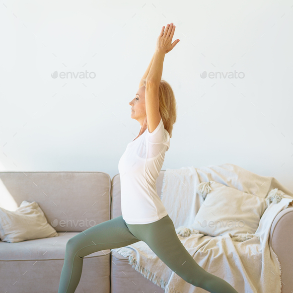 Focused retired mature women in sports wear practicing Warrior Yoga Pose at home - Stock Photo - Images