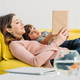 pretty smiling woman  with cute boy reading book while lying on sofa together - PhotoDune Item for Sale