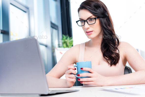 young brunette businesswoman working with laptop and holding coffee cup in office - Stock Photo - Images