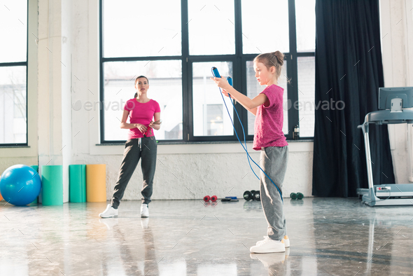 Full length view of mother looking at daughter exercising with skipping rope in gym - Stock Photo - Images