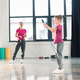Full length view of mother looking at daughter exercising with skipping rope in gym - PhotoDune Item for Sale