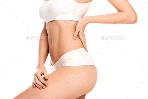 cropped view of young woman in top and panties standing with hand on hip isolated on white - Stock Photo - Images