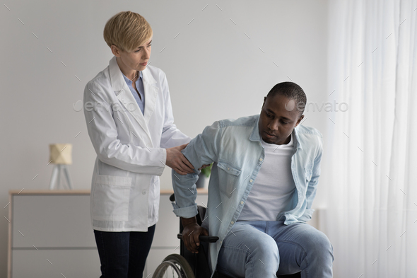 Serious female therapist in white coat looks at mature african american to disabled man - Stock Photo - Images