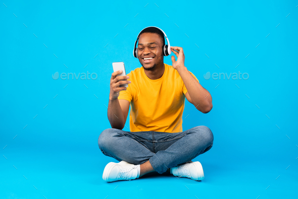 African Guy Listening Music Using Smartphone Wearing Headphones, Blue Background - Stock Photo - Images