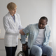 Serious female therapist in white coat looks at mature african american to disabled man - PhotoDune Item for Sale