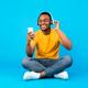 African Guy Listening Music Using Smartphone Wearing Headphones, Blue Background - PhotoDune Item for Sale