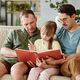 Gay parents reading a book to child - PhotoDune Item for Sale