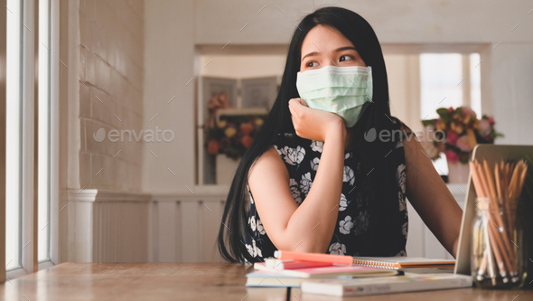 Tired woman wearing a medical mask looks out the window, with laptop and stationery on the table. - Stock Photo - Images