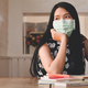 Tired woman wearing a medical mask looks out the window, with laptop and stationery on the table. - PhotoDune Item for Sale