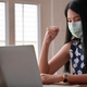 Woman in medical mask raising her fist with laptop on desk while working from home, Work from home. - PhotoDune Item for Sale