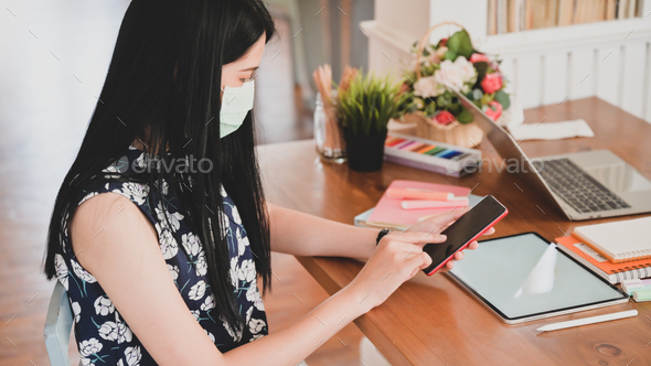 Woman wearing a medical mask is using a smartphone with a tablet. - Stock Photo - Images