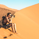 Lonely man photographer sitting on sand at Dune 45 in Sossusvlei - PhotoDune Item for Sale