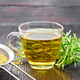 Tea of rosemary in cup with strainer on dark board - PhotoDune Item for Sale
