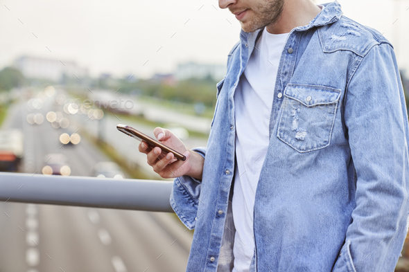 Close up of unrecognizable man holding mobile phone outdoors - Stock Photo - Images