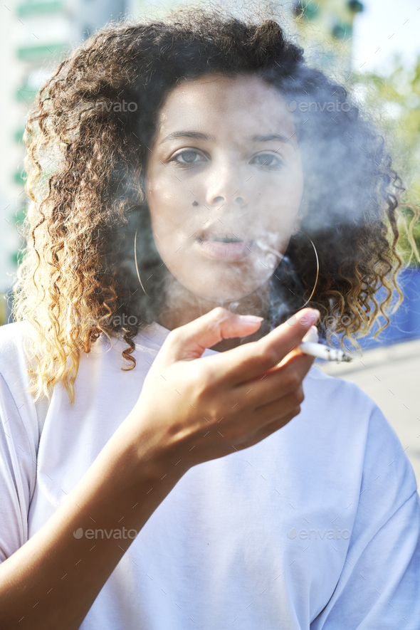 Portrait of young woman smoking cigarette - Stock Photo - Images