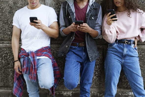 Front view of unrecognizable young people standing with mobile phones - Stock Photo - Images