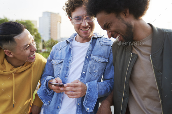 Three young men laughing at something holding mobile phone - Stock Photo - Images